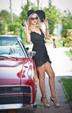 Summer portrait of stylish blonde vintage woman with long legs posing near red retro car. fashionable attractive fair hair female Stock Image