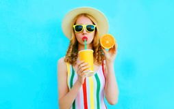 Summer portrait woman drinking fruit juice holding in her hand slice of orange in straw hat on colorful blue. Background royalty free stock photo