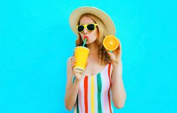 Summer portrait woman drinking fruit juice holding in her hand slice of orange in straw hat on colorful blue stock photo