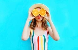 Summer portrait woman holding in her hands two slices of orange fruit hiding her eyes in straw hat on colorful blue. Background stock photos