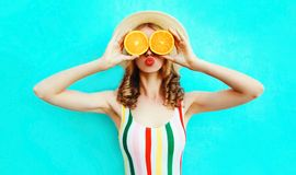 Summer portrait woman holding in her hands two slices of orange fruit hiding her eyes in straw hat on colorful blue royalty free stock photos