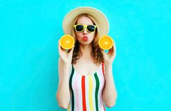 Summer portrait woman holding in her hands two slices of orange fruit in straw hat on colorful blue royalty free stock images