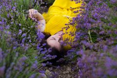 Summer portrait of young attractive woman in yellow dress lying in blooming violet lavander field stock images