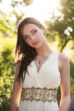 Summer portrait of young beautiful lady wearing long white evening dress posing in the park. Graduate Girl stock images