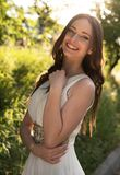 Summer portrait of young beautiful lady wearing long white evening dress posing in the park. Royalty Free Stock Image