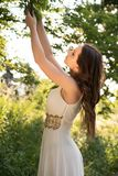 Summer portrait of young beautiful lady wearing long white evening dress posing in the park. Royalty Free Stock Images