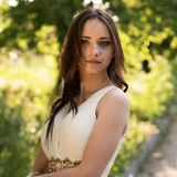 Summer portrait of young beautiful lady wearing long white evening dress posing in the park. Graduate Girl royalty free stock photos
