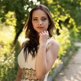 Summer portrait of young beautiful lady wearing long white evening dress posing in the park. Royalty Free Stock Photography