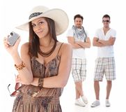Summer portrait of young woman with men behind Royalty Free Stock Photos