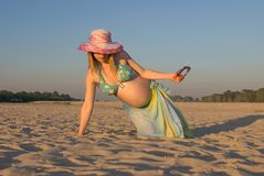 Summer pregnancy. During pregnancy the help everywhere (even on a beach) is necessary to the woman Royalty Free Stock Image
