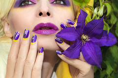 Summer purple yellow makeup and manicure . Summer purple yellow makeup and manicure with design on long square nails on the woman with the flower Clematis royalty free stock images