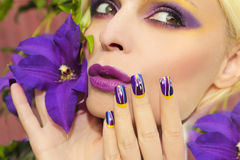 Summer purple yellow makeup and manicure . Summer purple yellow makeup and manicure with design on long square nails on the woman with the flower Clematis stock photography