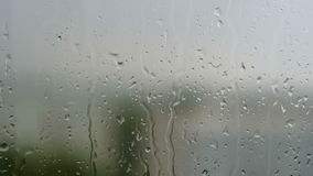 Summer quiet rain outside the window. Drops of water slowly flow down the glass. The rain knocks on the windowsill. stock footage