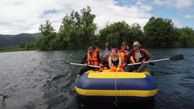 Summer rafting: group of tourists and travelers floating on calm river on raft