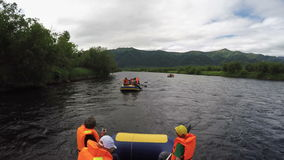 Summer rafting on Kamchatka Peninsula - group of tourists and travelers floating on river on raft. BYSTRAYA RIVER, KAMCHATKA PENINSULA, RUSSIA - JULY 13, 2016 stock video