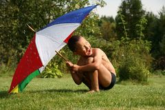 Summer rain. Little boy under umbrella in summer rain Stock Images