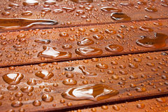 Summer rain on deck. A close up on a recently sealed cottage deck just after the summer rain.  Water beads up in reflective pools as the sun begins to shine Royalty Free Stock Images