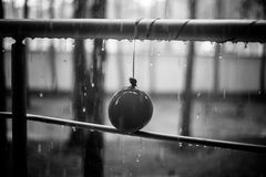 Droplets on the balloon and metal handrail, black and white photo. Summer rain, droplets on metal handrail. After party concept stock photography