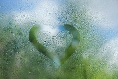 Summer rain drops on window glass background texture. the heart. Is drawn with a finger on the glass Stock Photos