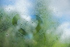 Summer rain drops on window glass background texture. the heart. Is drawn with a finger on the glass Royalty Free Stock Photography
