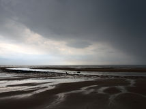 A summer rain storm on a beach with dramatic clouds Royalty Free Stock Photography