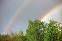 Summer rain and twin rainbow Stock Photo