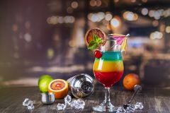 Summer rainbow layered cocktail. Glass of layered rainbow summer cocktail decorated with cherry and slice of red orange. Exotic summer drink on a bar counter royalty free stock images