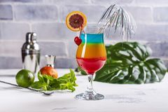 Summer rainbow layered cocktail. Glass of layered rainbow summer cocktail decorated with cherry and slice of red orange. Exotic summer drink. Copy space stock photography