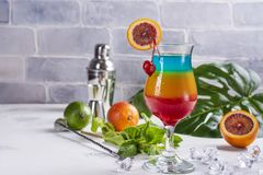 Summer rainbow layered cocktail. Glass of layered rainbow summer cocktail decorated with cherry and slice of red orange. Exotic summer drink. Copy space royalty free stock image