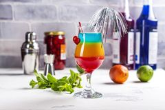 Summer rainbow layered cocktail. Glass of layered rainbow summer cocktail decorated with cherry and slice of red orange. Exotic summer drink with grenadine and stock photography
