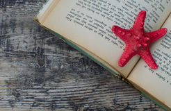 Summer reading. Starfish and a book on a wooden background with a copyspace Royalty Free Stock Photos