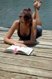 Summer reading. A girl reading a book by the lake on a dock royalty free stock photography