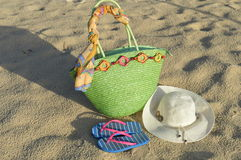 Summer ready. Summer must haves, green woven bag, straw hat, flipflops, beach, white sand, hat Stock Photo