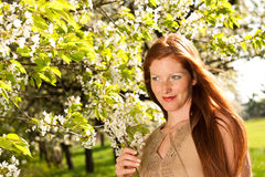 Summer - red hair woman under blossom tree Royalty Free Stock Images