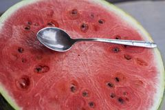Summer red surface of fresh watermelon with an old teaspoon. On it close-up Royalty Free Stock Photo