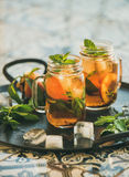 Summer refreshing cold peach ice tea with mint, copy space Royalty Free Stock Image