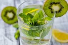 Summer refreshing drink in a glass with straw close-up. Cold sweet and sour lemonade with cubes of lemon, kiwi, mint and ice stock photography