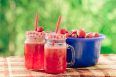 Summer refreshing drink homemade lemonade with strawberries in glasses with a straw stock image