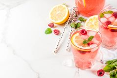 Raspberry mojito or lemonade. Summer refreshing drinks, fruit and berry raspberry mojito or lemonade with fresh mint, frozen raspberries, slices of lemon, ice Royalty Free Stock Images