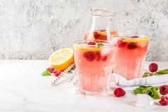 Raspberry mojito or lemonade. Summer refreshing drinks, fruit and berry raspberry mojito or lemonade with fresh mint, frozen raspberries, slices of lemon, ice Stock Images