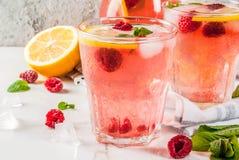 Raspberry mojito or lemonade. Summer refreshing drinks, fruit and berry raspberry mojito or lemonade with fresh mint, frozen raspberries, slices of lemon, ice Royalty Free Stock Photography