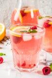 Raspberry mojito or lemonade. Summer refreshing drinks, fruit and berry raspberry mojito or lemonade with fresh mint, frozen raspberries, slices of lemon, ice Stock Photos