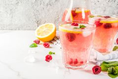 Raspberry mojito or lemonade. Summer refreshing drinks, fruit and berry raspberry mojito or lemonade with fresh mint, frozen raspberries, slices of lemon, ice Stock Photography
