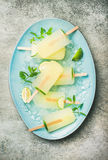 Summer refreshing lemonade popsicles with lime and chipped ice. Summer refreshing lemonade popsicles with lime and mint with chipped ice on blue plate over grey Royalty Free Stock Image