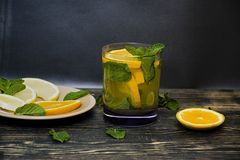 Summer, refreshing orange drink with mint and orange slices. Dark wooden background. Side view royalty free stock image