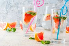 Summer refreshment grapefruit drink. Summer refreshment detox water drink with Pink grapefruit and fresh mint, spa fruit water, lemonade or jin tonic cocktail Royalty Free Stock Photos