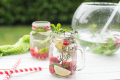Summer refreshment drink. Water with raspberry, lime, ice and mint on rustic background. Royalty Free Stock Image
