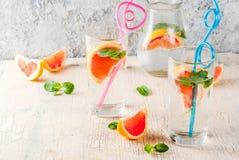 Summer refreshment grapefruit drink. Summer refreshment detox water drink with Pink grapefruit and fresh mint, spa fruit water, lemonade or jin tonic cocktail Royalty Free Stock Images
