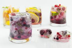 Summer refreshment next to frozen fruit in ice cubes on white ba Stock Images
