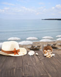 Summer, and relax. Summer, hat, seashells on table Royalty Free Stock Image